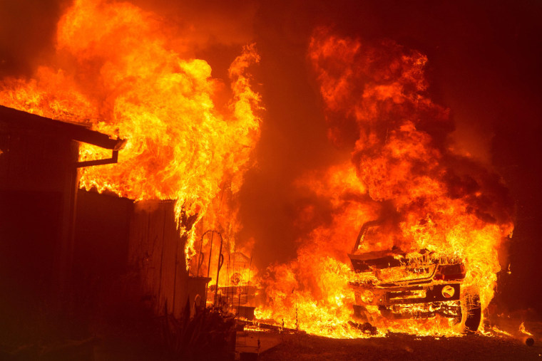 """Image:  A car and house are engulfed in flames as the \""""Wall Fire\"""" burns through a residential area in Oroville"""
