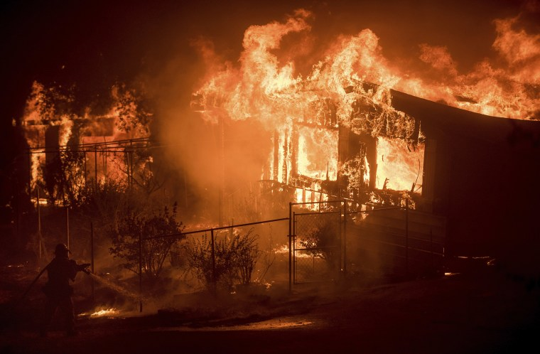 Image: A firefighter sprays water as flames from a wildfire consume a residence near Oroville, Calif.