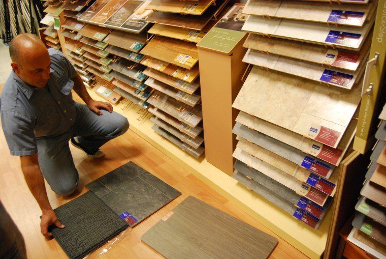 Darlene Horn's husband picking out flooring for their home.
