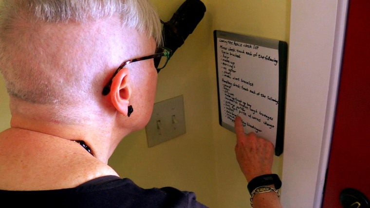 Gerda Saunders looks at a list she posted to help her when she forgets how to do simple tasks.