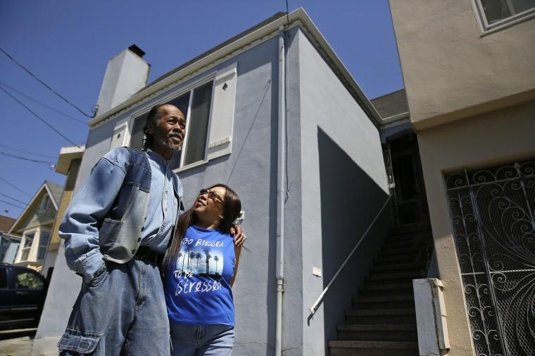 Image: Graciano and Buena de la Cruz stand outside their home in San Francisco
