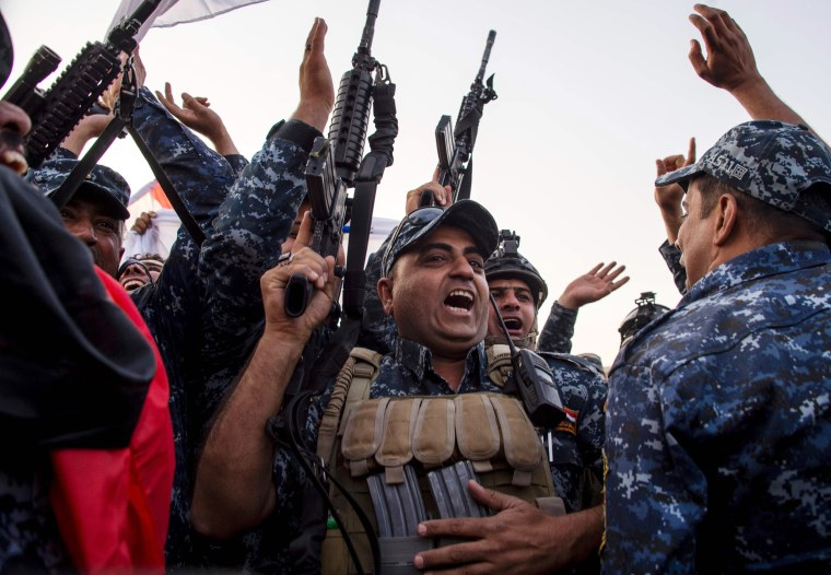 Image: Members of the Iraqi federal police forces celebrate in the Old City of Mosul