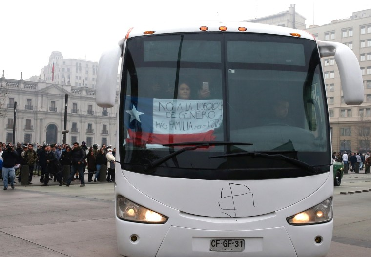 "Image: A woman holds a national flag with the words ""No to transgender ideology, more family, less state"" while riding on a bus of conservative advocacy group Citizen Go in Santiago"