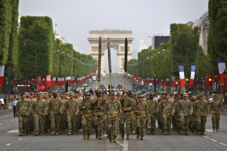 Image: Members of U.S. army 1st Division, U.S. air force, U.S. Navy and U.S. Marines, march down during a rehearsal for the French Bastille Day parade