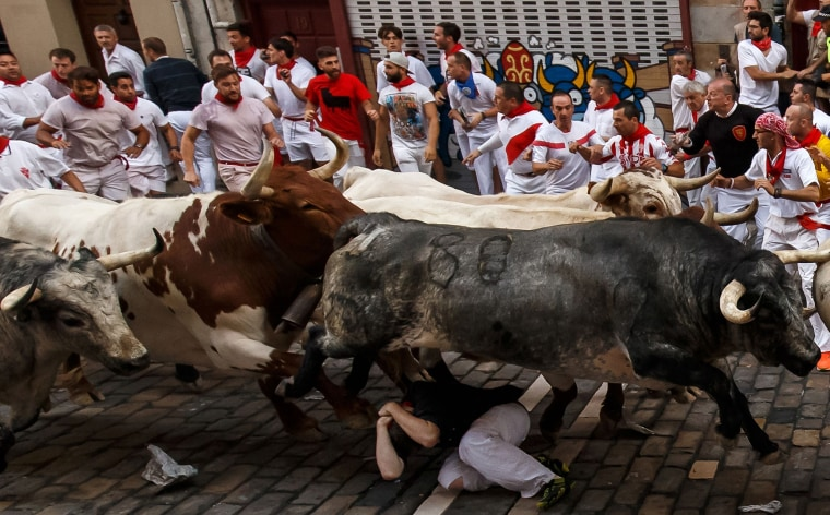 Image: A runner falls under a fighting bull