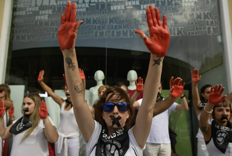 Image: Anti bullfight protesters hold up their hands