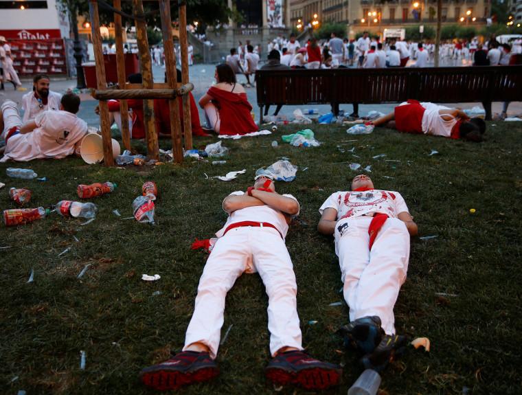 Image: Revelers sleep on the grass