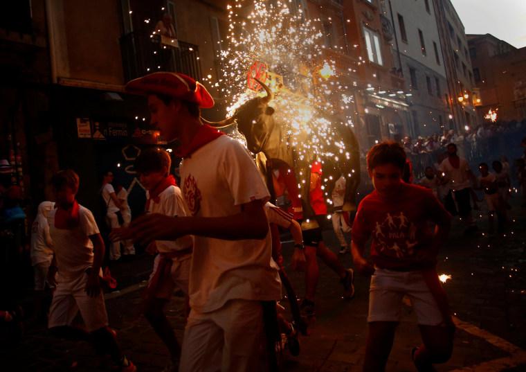 Image: Revelers run from the Fire Bull