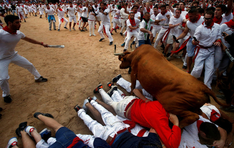 Image: A wild cow leaps over revelers in the bull ring