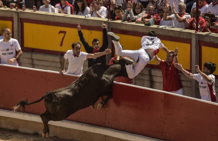 Image: A man jumps the bull ring barrier