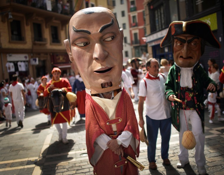 Image: Giant-headed figures, known as Kilikis, parade on the street on Saint Fermin's day at the San Fermin festival in Pamplona