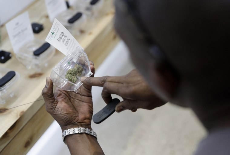 Image: A man examines marijuana for sale at The Source dispensary