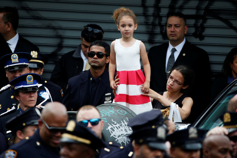 Image: A young girl is lifted above the crowd as police officers gather for the funeral service for slain New York City Police Department (NYPD) officer Miosotis Familia in the Bronx borough of New York City