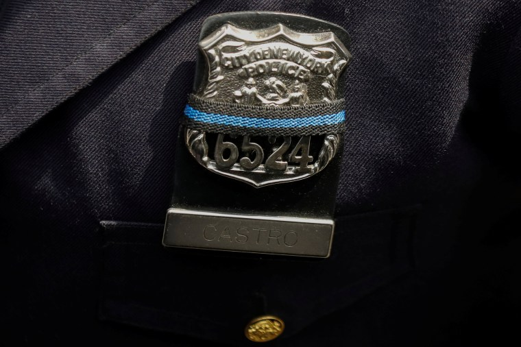 Image: An officer wears an NYPD Police shield covered with a mourning band as officers gather for the funeral service for slain New York City Police Department (NYPD) officer Miosotis Familia in the Bronx borough of New York City