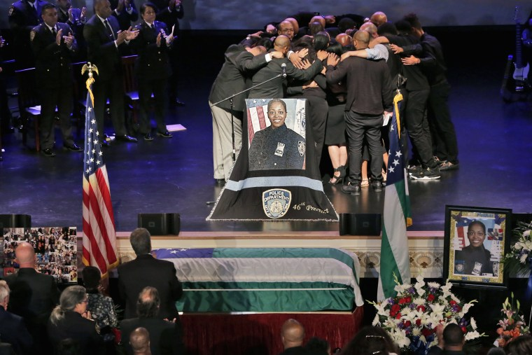 Image: The family of New York City Police officer Miosotis Familia hug during her funeral