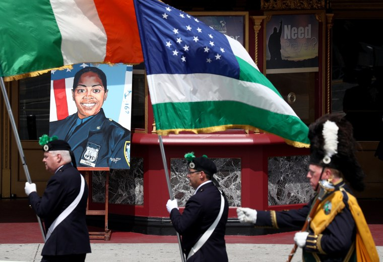 Image:  Flags are carried past a photo of slain New York Police Department Officer Miosotis Familia
