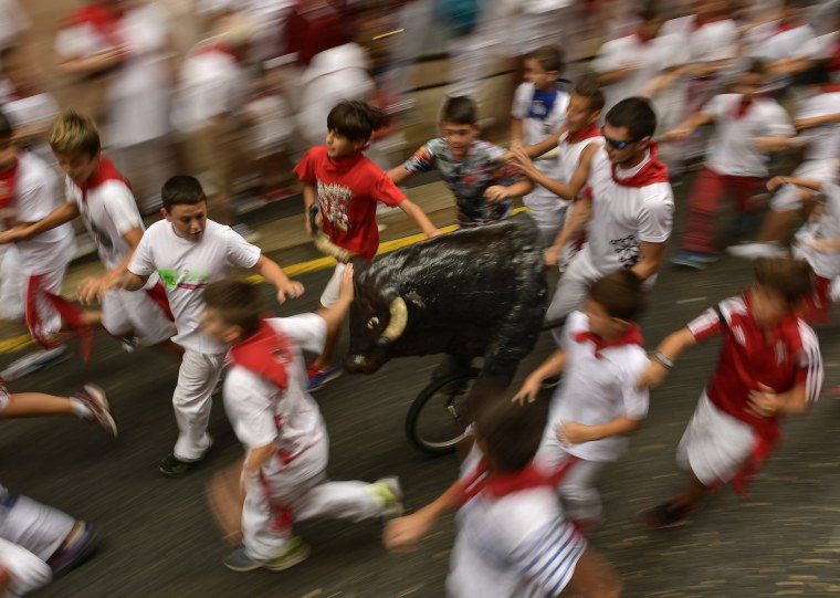 Image: Young boys run next to a toy bull