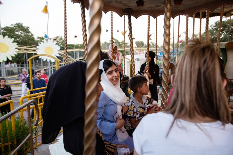 Image: Malala Yousafzai visits an amusement park and rides a carousel with children displaced by ISIS conflict