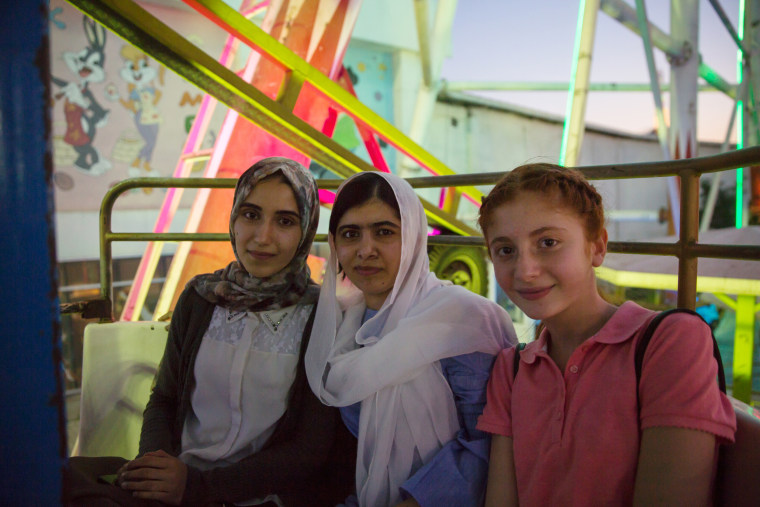 Image: Malala Yousafzai visits an amusement park and rides a ferris wheel with children displaced by ISIS conflict