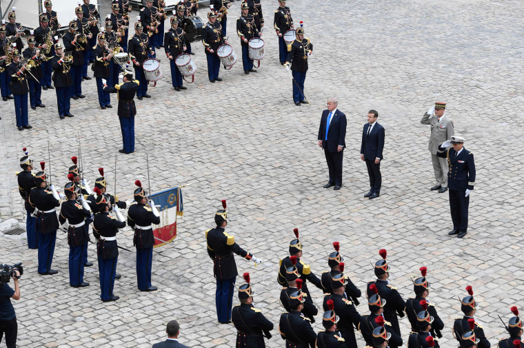 Image: President Donald Trump and French President Emmanuel Macron stand during a welcome ceremony
