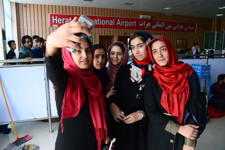 Image: Afghan teenagers from the Afghanistan Robotic House take pictures with a mobile phone at Herat International Airport, before embarking for the United States