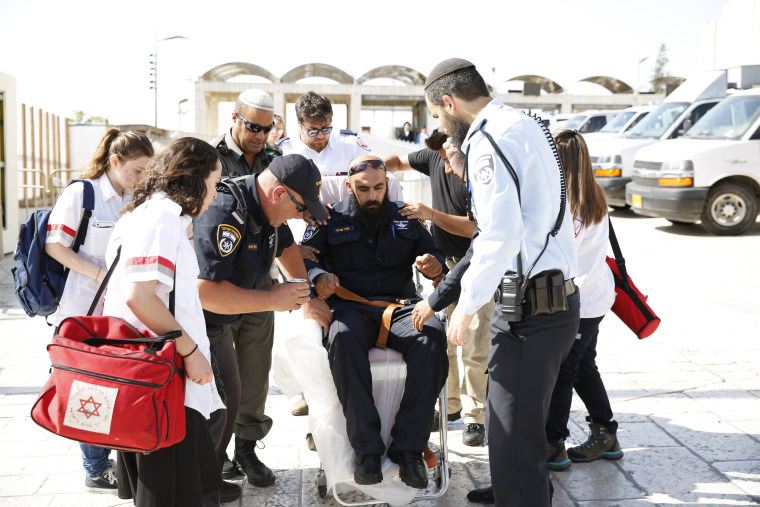 Image: An Israeli policeman is evacuated from the Temple Mount compound in Jerusalem's Old City