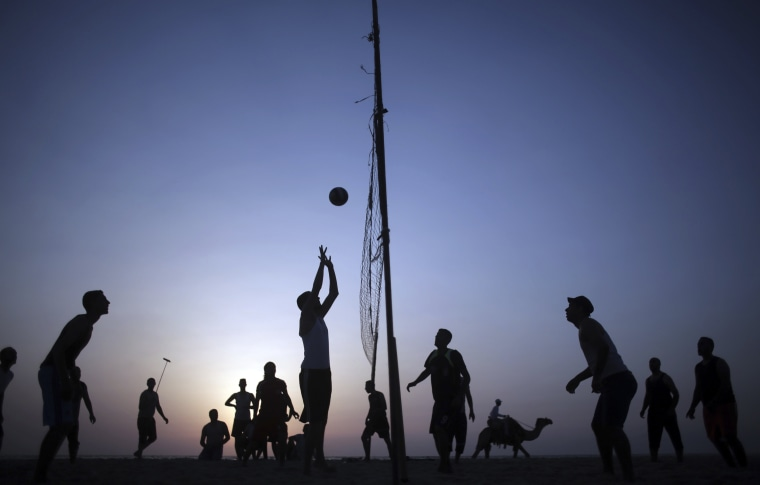 Image: Palestinians play volleyball on the beach as the sun sets over Gaza City