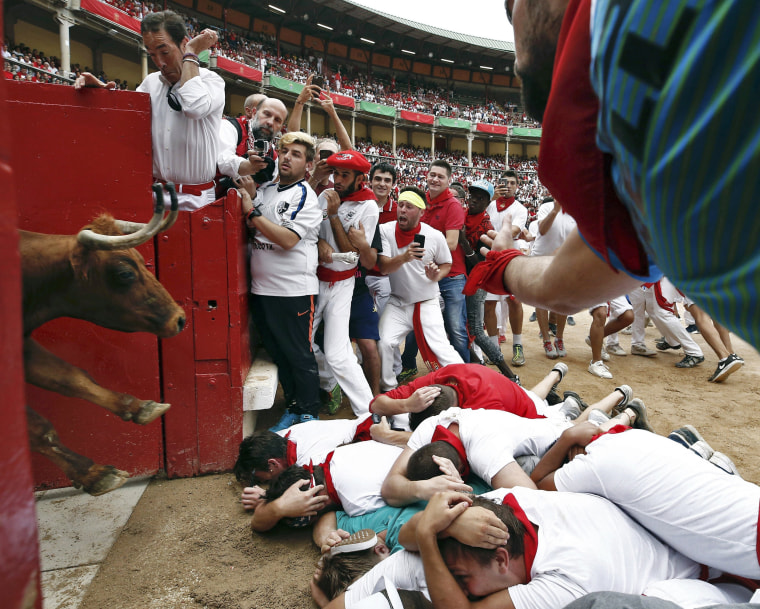 Image: A bull enters the ring as a group of runners protect themselves in Pamplona