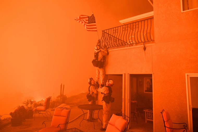 "Image:  Firefighters remove a US flag as flames from the ""Wall Fire"" close in on a luxury home in Oroville"