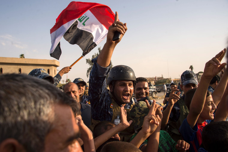 Image: Iraq's federal police members wave Iraq's national flag as they celebrate in the Old City of Mosul