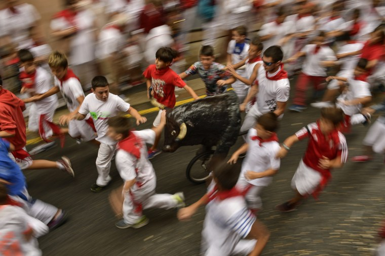 "Image: Boys run next to a toy bull during the ""Little Bull Run"" at the San Fermin Festival"