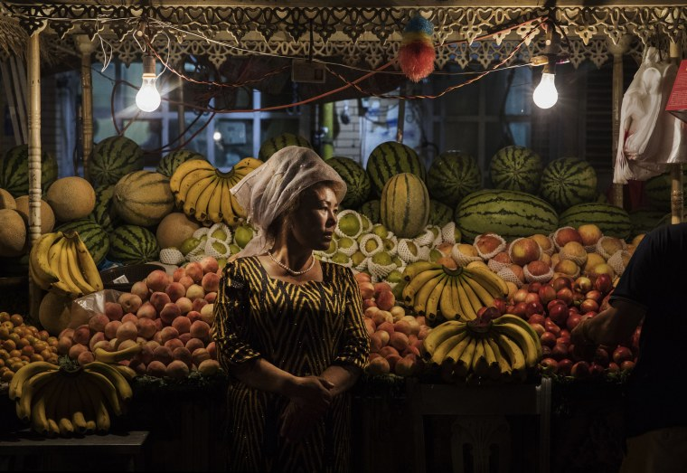 Image: An ethnic Uyghur woman waits for customers at her fruit stand
