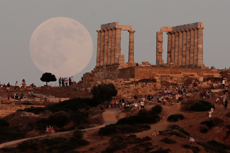 Image: A nearly full moon rises over the Temple of Poseidon, the ancient Greek god of the seas, in Cape Sounion, east of Athens