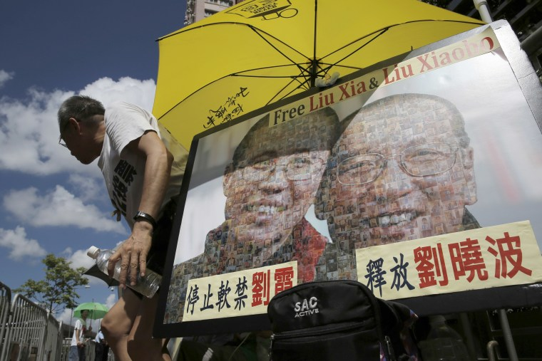 A protester displays a portrait of jailed Chinese Nobel Peace laureate Liu Xiaobo and his detained wife Liu Xia during a demonstration outside the Chinese liaison office in Hong Kong, Tuesday, July 11, 2017.