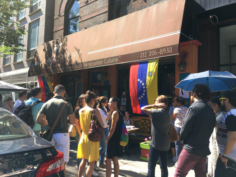 "In New York City, Venezuelans gather in front of the ""El Cocotero"" restaurant, one of the polling places in Sunday's vote."