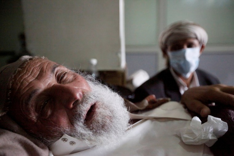 Image:   An old man infected with cholera lies on the bed at a hospital in Sanaa,