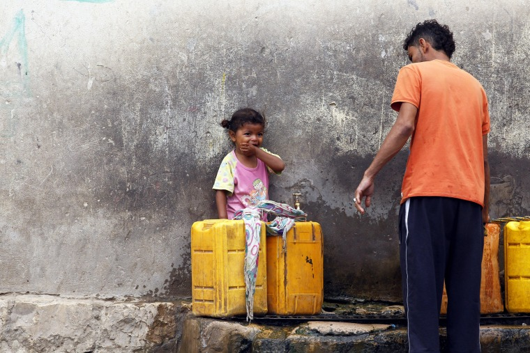 Image:  A Yemeni child looks on as a man fills jerrycans with drinking water from a donated water pipe