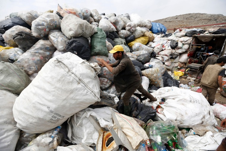 Image: A Yemeni man scavenges for recyclable items at a garbage dump