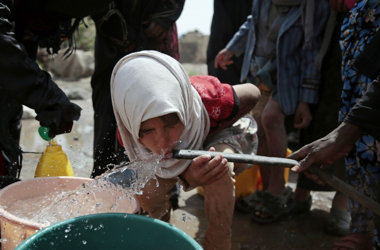 Image: A girl drinks water from a well that is allegedly contaminated with cholera bacteria,