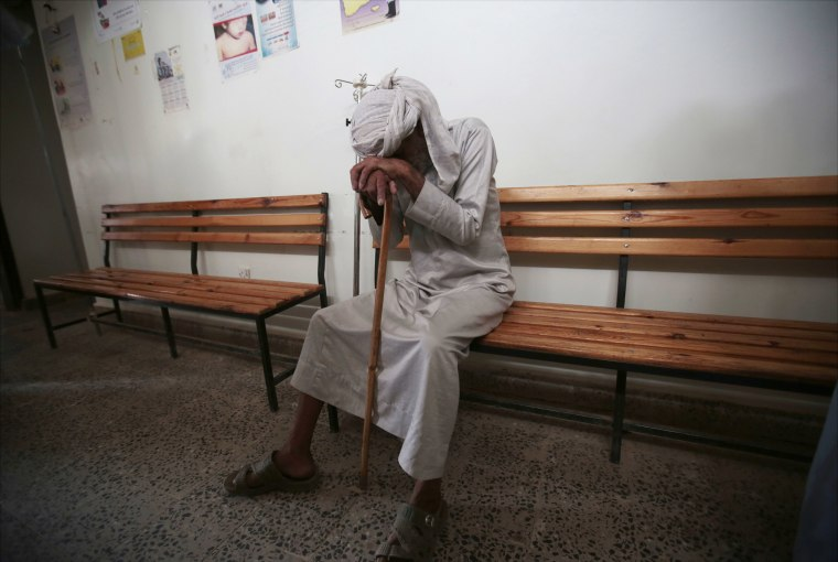 Image: An elderly man waits to be treated for a suspected cholera infection at a hospital in Sanaa