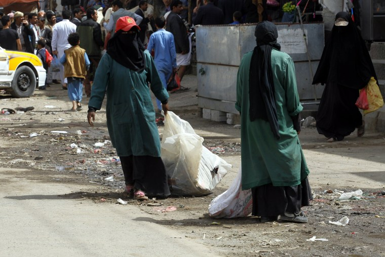 Image: Yemeni sanitation workers clean up a street in a residential area