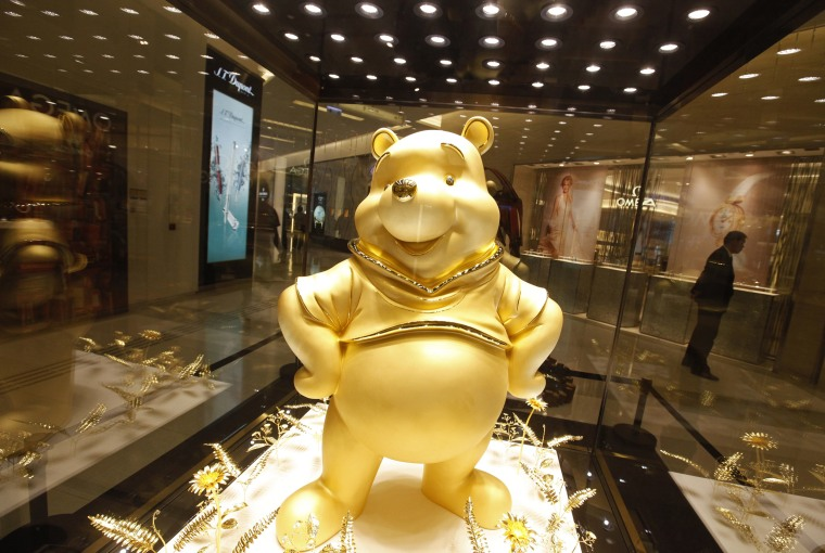 Image: A giant pure gold statue of the Disney character Winnie the Pooh is on display at a shopping mall in Hong Kong