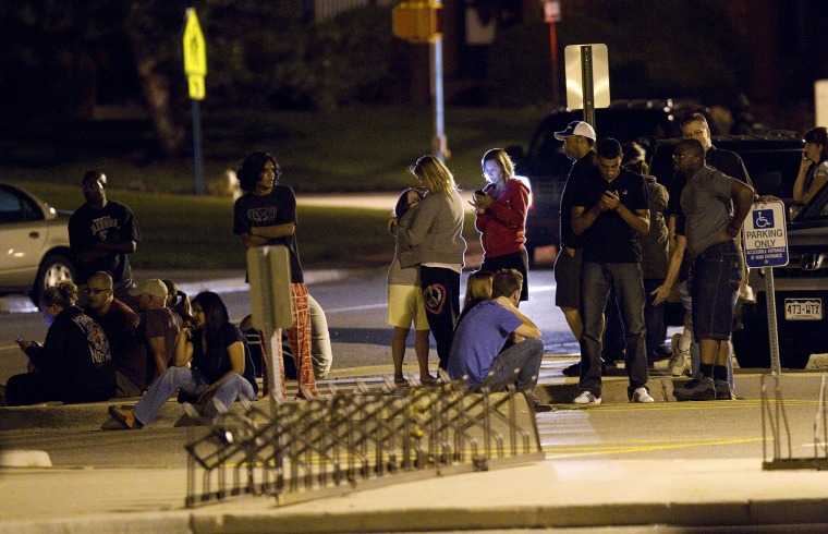 Image: Family and friends wait outside Gateway High School in Aurora