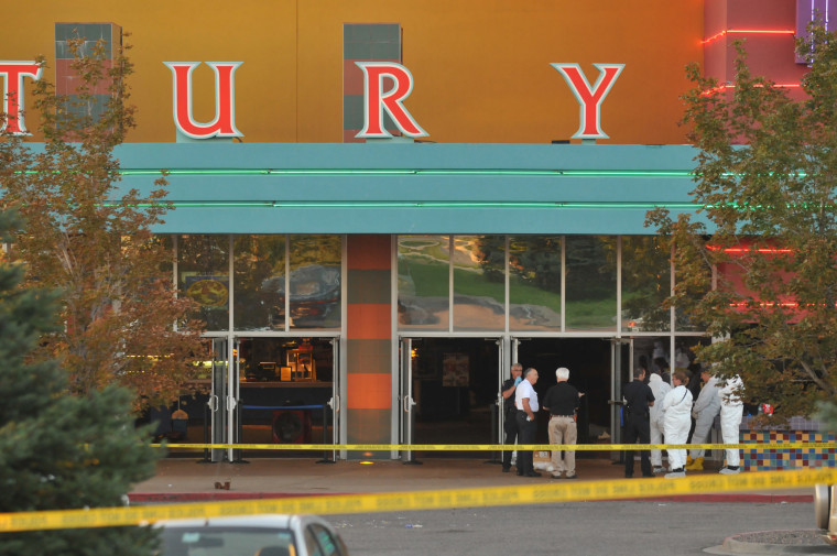 Image: Investigators work at the movie theater