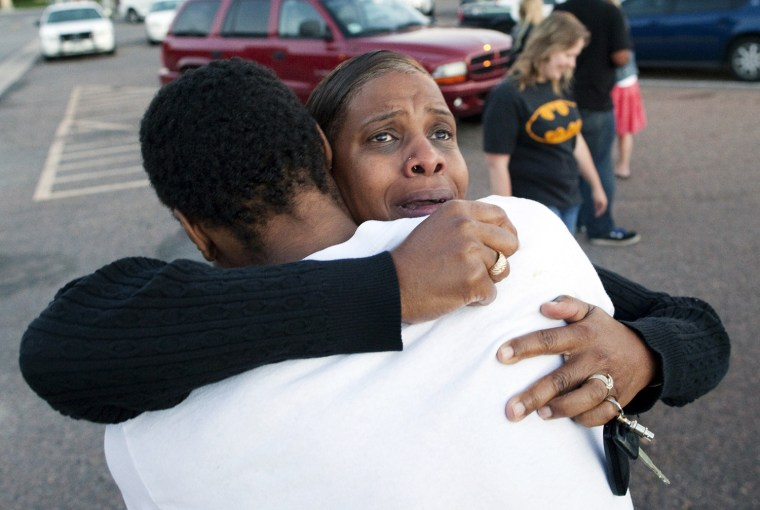 Image: Shamecca Davis hugs her son, Isaiah Bow, a witness to the shooting, outside Gateway High School