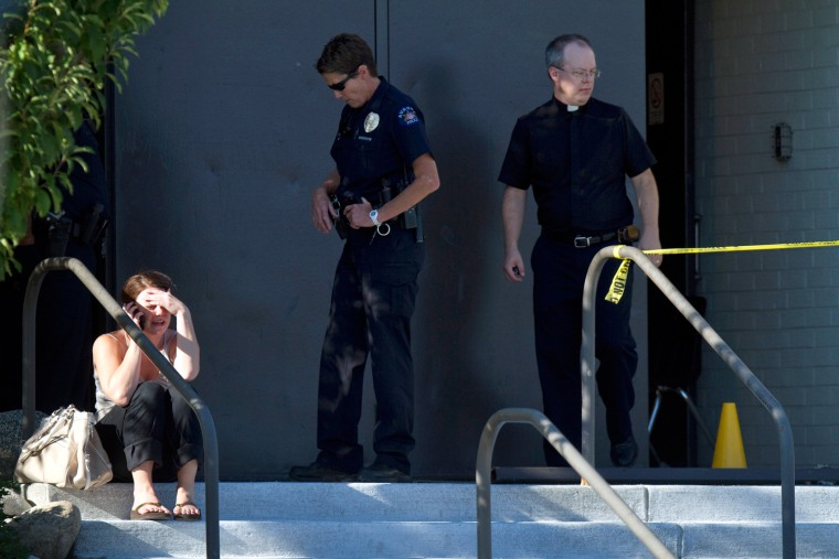 Image: A woman uses a cell phone as she sits on the steps near a police officer and a priest outside Gateway High School