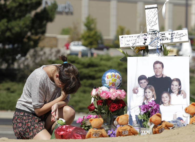 Image: Ashley Deuell, kneels next to a cross and a family photo of Gordon Cowden