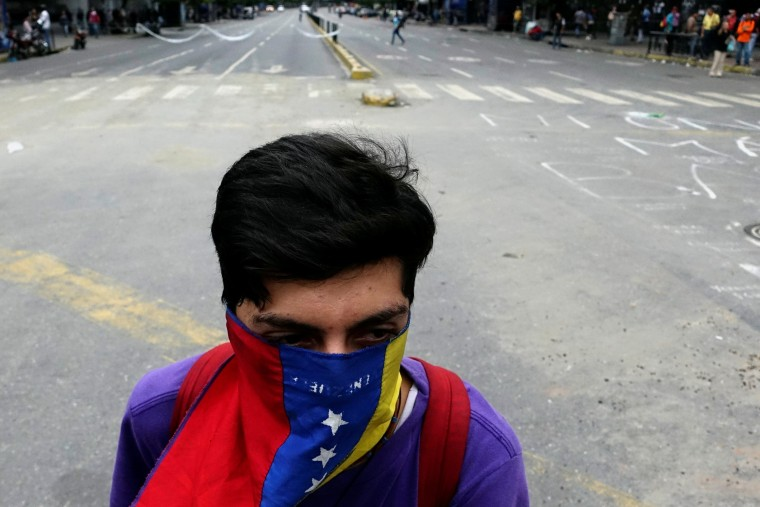 Image: A demonstrator wearing a Venezuelan national flag takes part in a protest against Venezuelan President Nicolas Maduro's government in Caracas