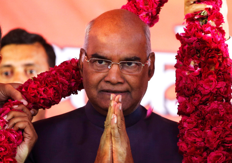 Image: Supporters of Ram Nath Kovind present him with a garland during a welcoming ceremony as part of his nation-wide tour in Ahmedabad