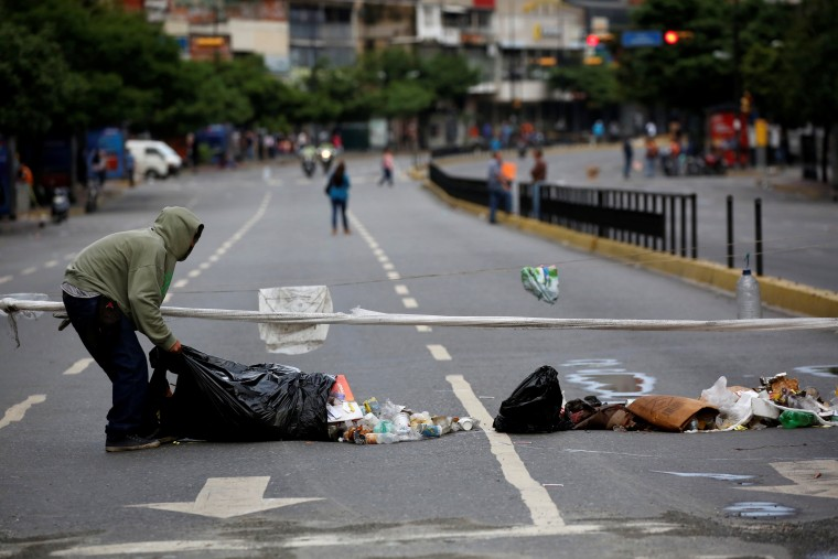 Image: A man uses garbage to block a street during a strike called to protest against Venezuelan President Nicolas Maduro's government in Caracas